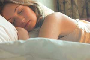 Woman sleeping soundly after using one of the herbal remedies for insomnia.