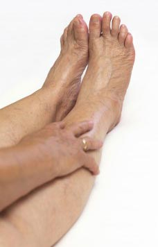 Woman is experiencing restless leg syndrome symptoms.