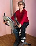 Woman is exercising on an indoor bike to avoid night leg cramps