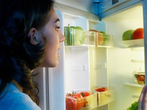 a woman looking in the fridge for foods that help you sleep